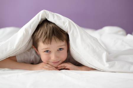 coverlet: Happy boy hiding in bed under a white blanket or coverlet. Boy at bed. Child in bed
