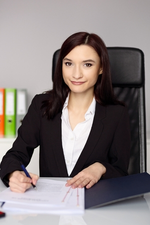 signing authority: Smiling woman notary public notarizes the power of attorney or other document . Notary public concept