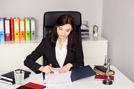 signing authority: Woman notary public stamping the document in her office. Notary public concept
