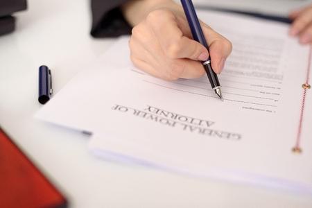 abogado: Primer plano de la mano de una mujer llenando un poder de representaci�n. concepto notario Foto de archivo