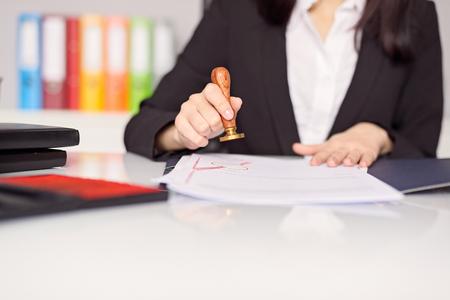 Close-up op vrouw notaris de hand afstempeling van het document. Notaris-concept Stockfoto