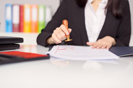 Zamknąć na kobiecej dłoni publicznego notariusza stemplowania dokumentu. Notariusz koncepcja publicznego