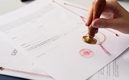 Feche com tinta de mão de notário público da mulher carimbando o documento. Conceito de notário público