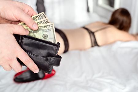 남자는 미국 돈 달러와 창녀를 지급합니다. 매춘부 개념