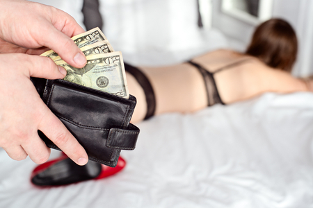 sex on bed: The man pays a prostitute with american money dollar . Prostitute concept