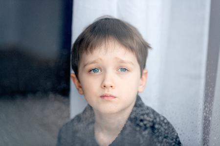 gotas de agua: Deprimido 7 años del niño chico mirando por la ventana. Día lluvioso. La soledad y el concepto de espera Foto de archivo