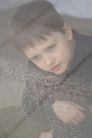 wet bear: Child is hugging his teddy bear. Sitting behind wet from rain window glass. Rainy Day. Loneliness and waiting concept Stock Photo