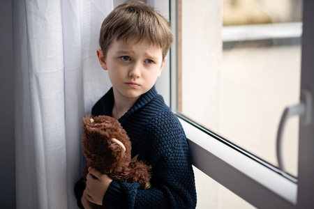 Boy is hugging his teddy bear. Standing by the window. Rainy Day. Loneliness and waiting concept