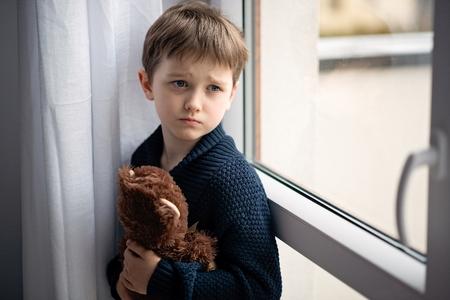 Chłopiec przytula swojego misia. Stojąc przy oknie. Deszczowy dzień. Samotność i koncepcja czekania