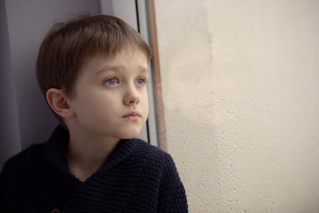 停止雨の] ウィンドウで待っている少年。孤独と待っている概念。雨の日