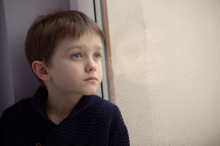 Boy waiting by window for stop raining. Loneliness and waiting concept. Rainy day