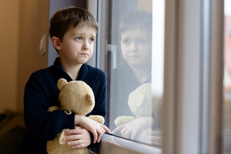 The little boy looks out the window. Rainy Day. Loneliness and waiting concept Stock Photo