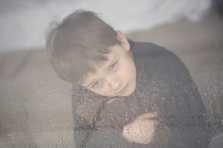 raindrops: Boy is hugging his teddy bear. Sitting behind wet from rain window glass. Rainy Day. Loneliness and waiting concept