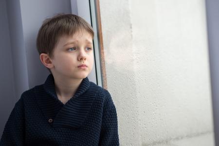 mirada triste: Sad 7 años del niño chico mirando por la ventana. Día lluvioso