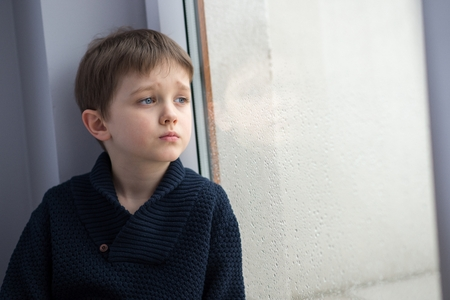 Sad 7 years boy child looking out the window. Rainy day