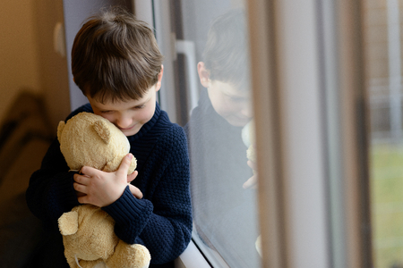 Sad boy is hugging his teddy bear. Standing by the window. Rainy Day. Loneliness and waiting concept Banco de Imagens