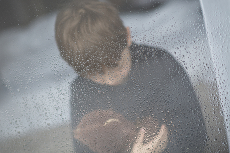 wet bear: The little boy is hugging his teddy bear. Selective focus.  Standing behind wet from rain window glass. Rainy Day. Loneliness and waiting concept Stock Photo