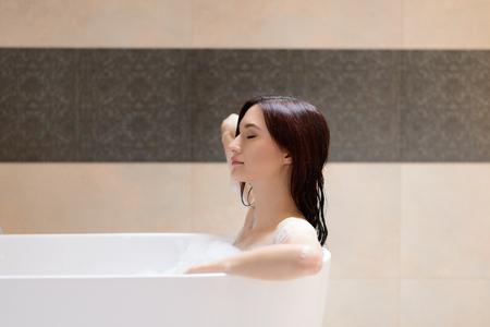 美しいブルネットの女性の浴槽でリラックス。浴室で女性 写真素材