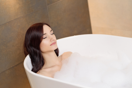 Young attractive brunette woman relaxing in bath with foam. Woman in bathroom