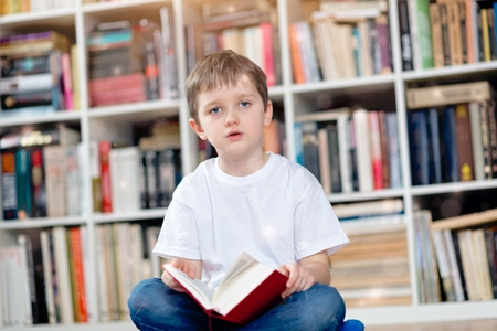crosslegged: Little boy with red book in the library. Looking at camera. He sits cross-legged on the floor. Dressed in a white t shirt and blue jeans Stock Photo