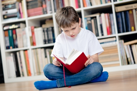 crosslegged: Child reading a red book in the library. He sits cross-legged on the floor. Dressed in a white t shirt and blue jeans Stock Photo