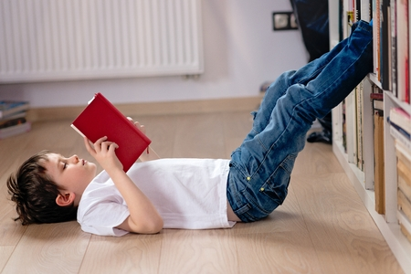 child education: Little boy child reading a book in the library. He lies on the floor. Legs on bookshelf Stock Photo
