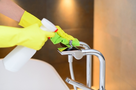 house cleaning: Female hands with yellow rubber protective gloves cleaning bath mixer with green cloth and spray detergent. Spring cleaning Stock Photo