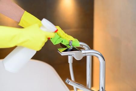 servicio domestico: Manos femeninas con guantes de goma amarilla de limpieza mezclador de baño con la tela verde y un detergente aerosol. Limpieza de primavera