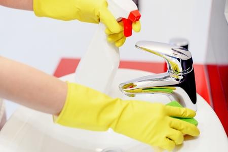 servicio domestico: Cierre plano de las manos con guantes de goma rociar detergente l�quido de barril y limpiarlo con una esponja. Limpieza de primavera