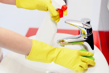 spring cleaning: Close up of female hands with rubber gloves spraying liquid detergent on tap and cleaning it with sponge. Spring cleaning