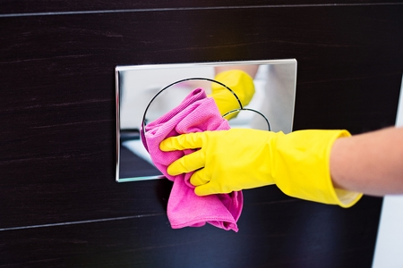 design house: Female hands with yellow rubber protective gloves cleaning toilet flush button with pink cloth. Spring cleaning