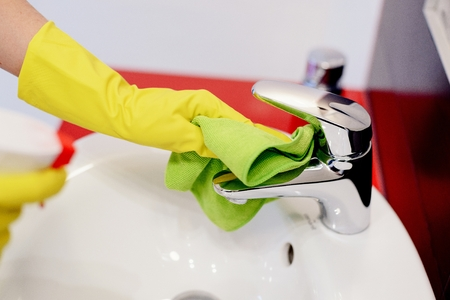 spring cleaning: Female hands with rubber protective gloves cleaning tap with green cloth. Spring cleaning