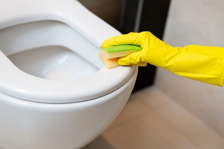 spring cleaning: Hands with yellow rubber gloves cleaning toilet in wc with yellow sponge. Spring cleaning Stock Photo