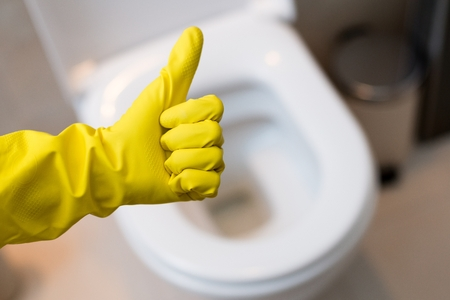 cleaning up: Close up of female hand with yellow protective rubber glove showing thumb up ok sign against clean toilet. Spring cleaning Stock Photo