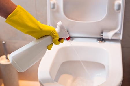 water pollution: Close up of female hand with yellow protective rubber glove cleaning toilet with spray antibacterial detergent . Spring cleaning