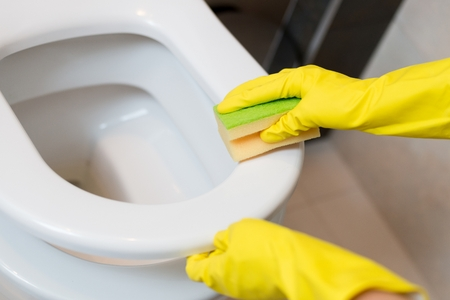spring cleaning: Female hands with yellow rubber gloves cleaning toilet seat in wc with yellow sponge. Spring cleaning Stock Photo