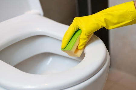 servicio domestico: Female hands with yellow rubber gloves cleaning toilet in wc with yellow sponge. Spring cleaning