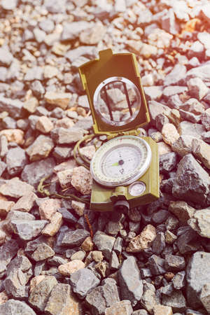 magnetic stones: Compass on gravel mountain hiking trail. Winter mountain trip concept