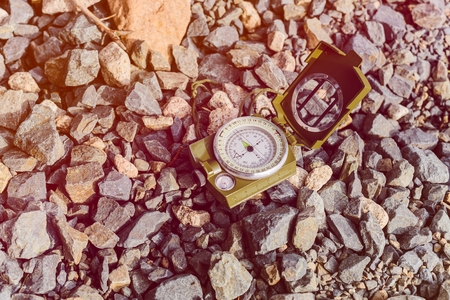 magnetic stones: Compass instrument on gravel mountain hiking trail. Winter mountain trip concept Stock Photo