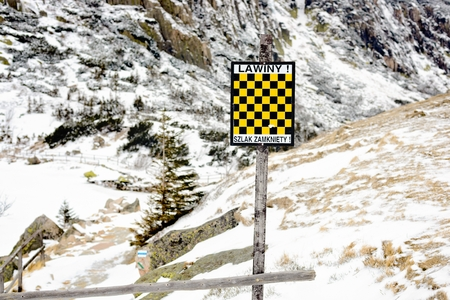avalanche: Black and Yellow  avalanche danger warning sign in the mountains - Polish inscription Avalanche Danger - trail closed Stock Photo
