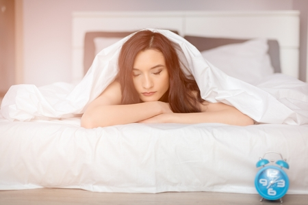 coverlet: beautiful brunette woman sleeping on her stomach covered by white coverlet. It is time to wake up Stock Photo