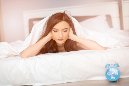 coverlet: Young beautiful brunette woman sleeping on her stomach covered by white coverlet. It is time to wake up . Covering ears with hands