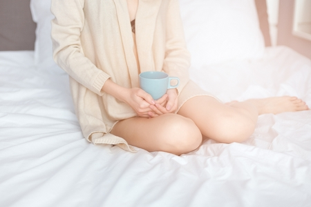 Young woman drinking her coffee while sitting on bed. Lazy sunny morning in bed. Dressed in beige sweater.
