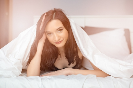 coverlet: Young beautiful brunette woman looking out from coverlet. Waking up at sunny morning.