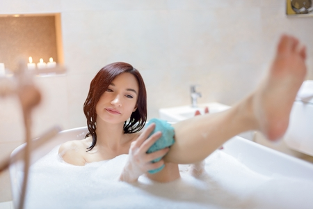 bathing women: Young brunette woman washing herself with sponge at bath with foam. Woman at bathroom. Stock Photo