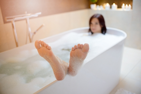 woman bath: Young brunette woman taking bath with her feet on the edge of the bathtub