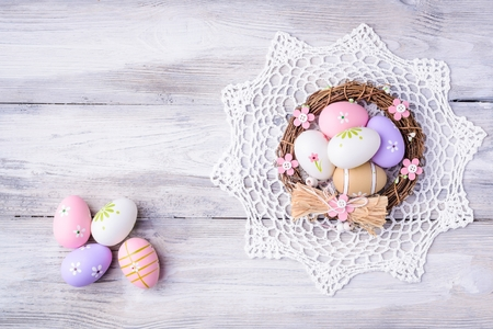 servilleta de papel: Colorful Easter eggs with white serviette and nest on old cracked wooden background. Copy space. Easter concept. Happy Easter !