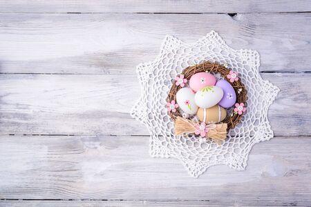 servilleta de papel: Huevos de Pascua coloridos con la servilleta blanca y anidan en viejo fondo de madera agrietada. Espacio de la copia. Concepto de Pascua. Felices Pascuas !