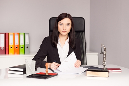 certifying: Brunette woman Notary Public signing testament. Law office concept.