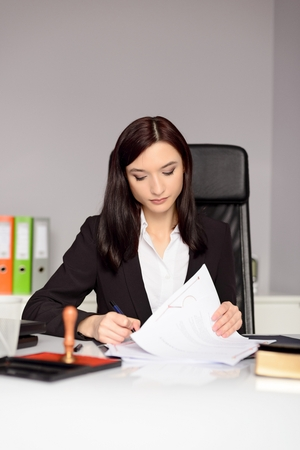 certifying: Brunette woman Notary Public reading testament. Law office concept.